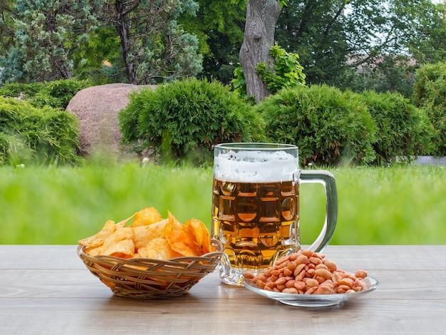 Chope de bière en verre sur une table en bois avec des croustilles dans un panier en osier, des cacahuètes dans une assiette sur un bureau en bois avec le fond vert de la ville.