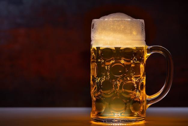 Chope pleine de bière avec une tête mousseuse dans un gros plan