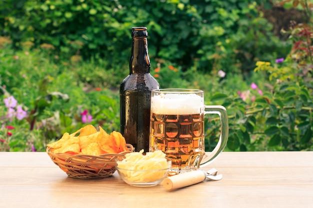 Chope en verre de bière et bouteille de bière sur une table en bois avec des croustilles dans un panier en osier, des calmars séchés dans un bol et un ouvre-porte