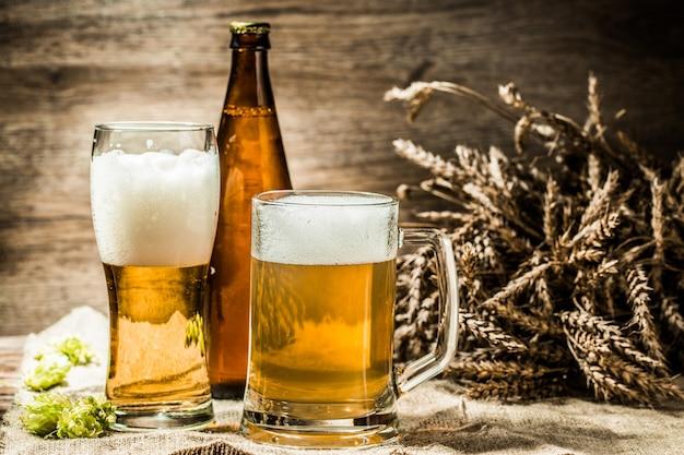 Chopes à bière, verres, bouteille sur toile avec houblon, blé