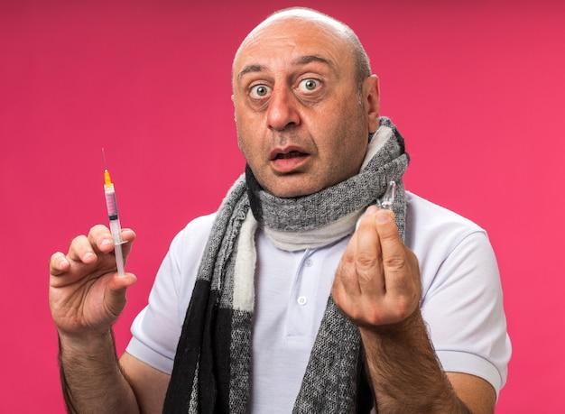 Choqué adulte malade caucasien homme avec écharpe autour du cou tenant la seringue et l'ampoule isolé sur mur rose avec copie espace