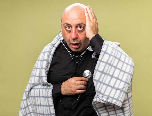 Choqué adulte malade caucasien homme enveloppé dans un plaid met la main sur la tête mesurant le rythme cardiaque avec stéthoscope isolé sur mur vert olive avec espace copie