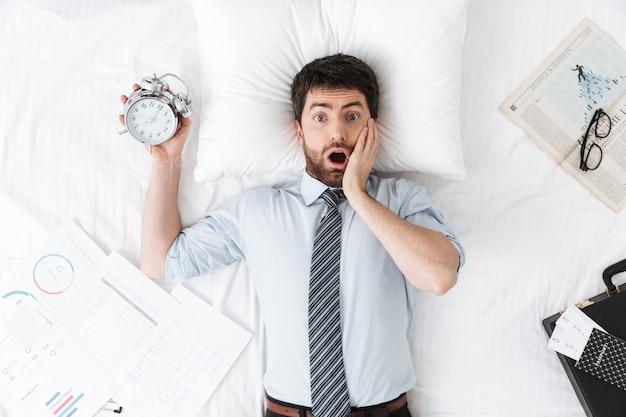 Choqué beau jeune homme d'affaires le matin au lit se trouve en train de dormir tenant un réveil