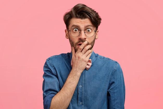 Choqué beau jeune homme couvre la bouche, a les yeux sortis, regarde à travers des lunettes, porte une chemise en jean