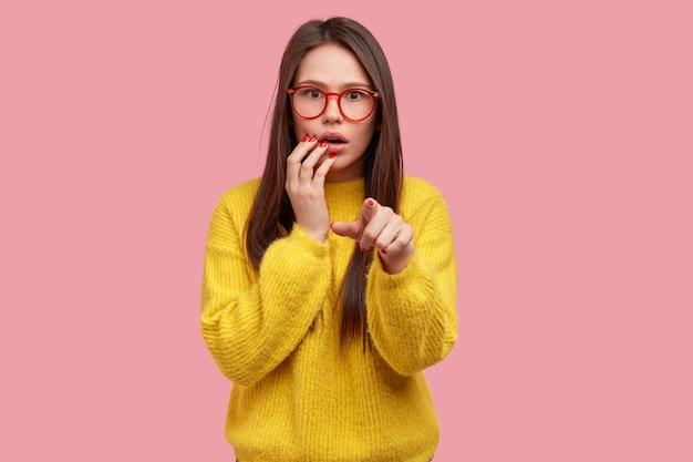 Choqué belle jeune femme avec une expression effrayée pointe vers vous, a regardé frustré inquiet, habillé en tenue jaune