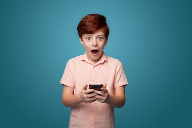 Choqué caucasina ginger boy tenant un téléphone et regardant directement sur un mur bleu