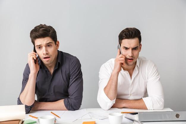 Choqué a confondu deux jeunes hommes d'affaires parlant au téléphone avec des téléphones portables.
