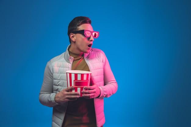 Choqué dans les lunettes 3d et avec du pop-corn. portrait d'un homme de race blanche isolé sur un mur de studio bleu
