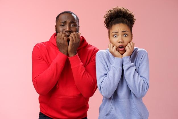 Choqué effrayé deux jeunes couples afro-américains peu sûrs d'eux deux araignées effrayées debout lit terrifié gelé de peur tenant les mains bouche mordant les doigts secouant l'horreur, fond rose