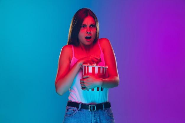 Choqué, effrayé, mangeant du pop-corn. portrait de jeune femme caucasienne sur fond dégradé à la lumière du néon. beau modèle féminin. concept d'émotions humaines, expression faciale, ventes, publicité, film, cinéma.