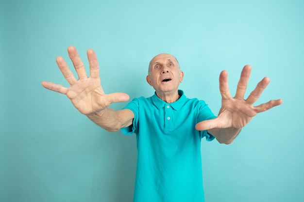 Choqué, effrayé. portrait d'homme senior caucasien sur studio bleu.