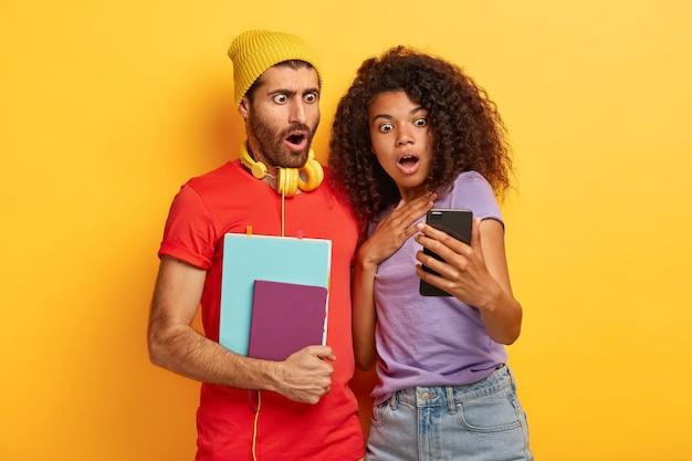 Choqué élégant couple posant contre le mur jaune avec des gadgets