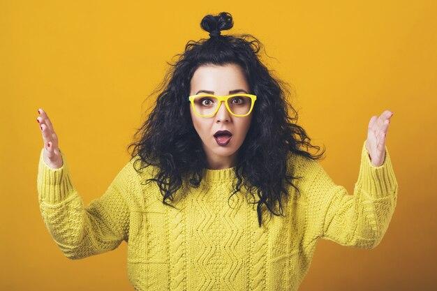 Choqué étonné jeune femme aux cheveux bouclés et lunettes