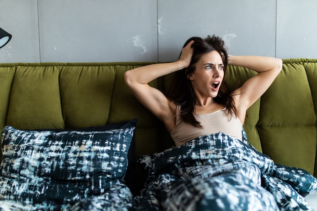 Choqué étonné de jeune femme se réveiller tard dans son lit blanc