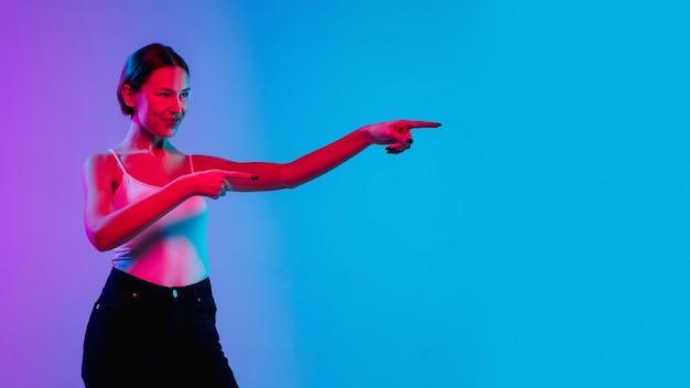 Choqué, étonné. portrait de jeune femme caucasienne sur fond de studio dégradé bleu-violet en néon. concept de jeunesse, émotions humaines, expression faciale, ventes, publicité. beau modèle brune.
