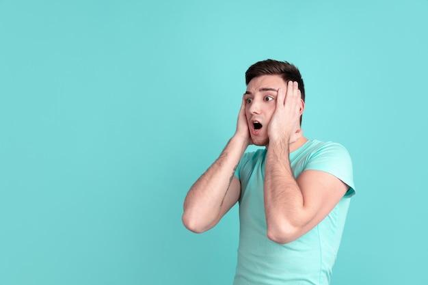 Choqué, étonné. portrait d'un jeune homme caucasien isolé sur un mur de studio bleu