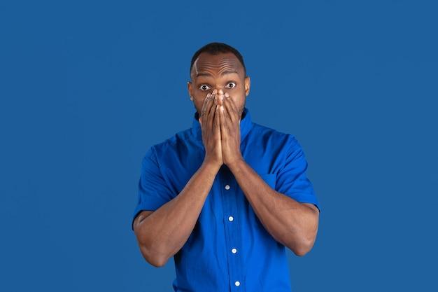 Choqué, étonné. portrait monochrome de jeune homme afro-américain isolé sur le mur bleu du studio.