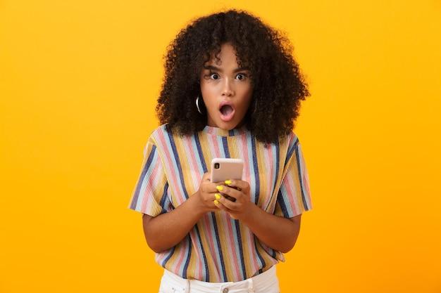 Choqué femme africaine émotionnelle posant isolé sur un espace jaune à l'aide de téléphone mobile.