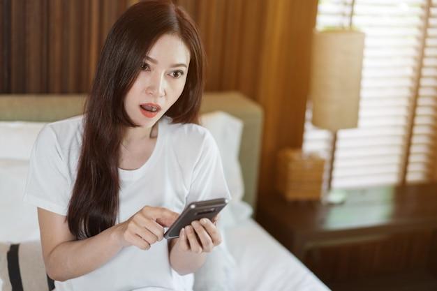 Choqué de femme à l'aide de téléphone portable sur un lit