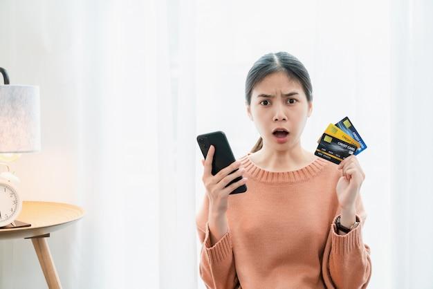 Choqué femme asiatique excitée tenant une carte de crédit et un smartphone, parce que beaucoup de dépenses.