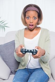 Choqué femme assise sur le canapé en jouant à des jeux vidéo