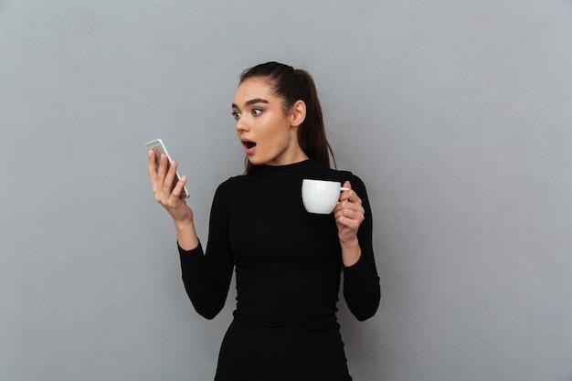 Choqué femme brune en vêtements noirs regardant smartphone