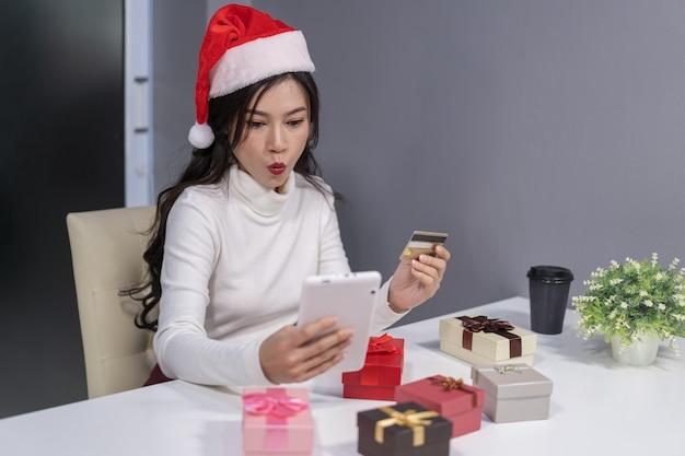 Choqué, femme, dans, santa hat, achats en ligne, pour, cadeau noël, à, tablette numérique