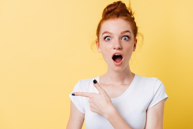 Choqué femme gingembre en t-shirt pointant loin