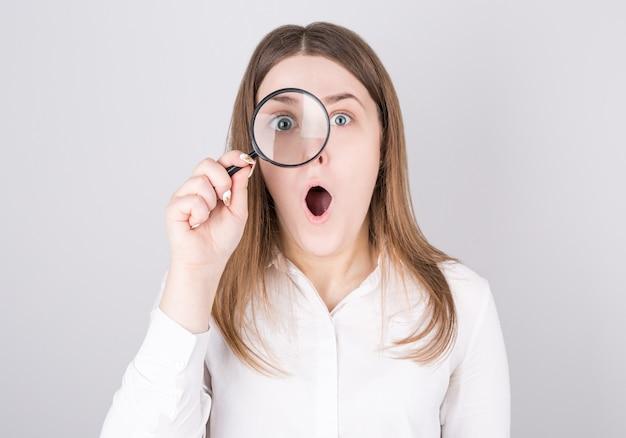 Choqué femme regardant à travers une loupe