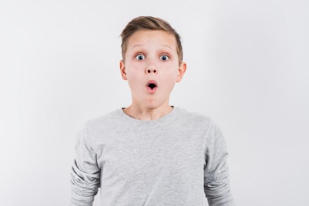 Choqué garçon à la recherche d'appareil photo sur fond gris