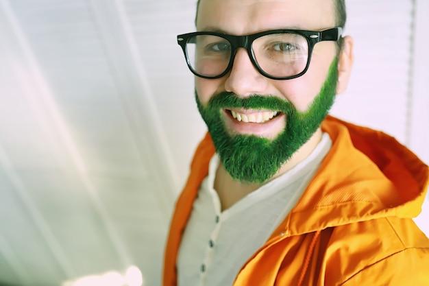Choqué et heureux. joyeuse saint patrick. homme barbu aux yeux grands ouverts célébrant la saint-patrick. hipster en chapeau et costume de lutin. irlandais avec barbe vêtu de vert.