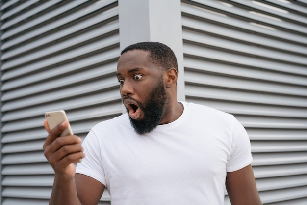 Choqué homme afro-américain avec la bouche ouverte à l'aide de téléphone mobile en regardant l'écran numérique. un mec étonné regarde les actualités en ligne