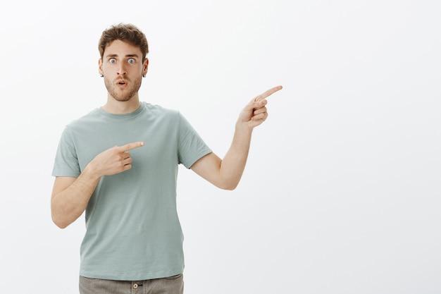 Choqué homme étonné d'entendre une terrible rumeur, d'en discuter et de pointer du doigt la personne qui a raconté la révélation, debout abasourdi et impressionné