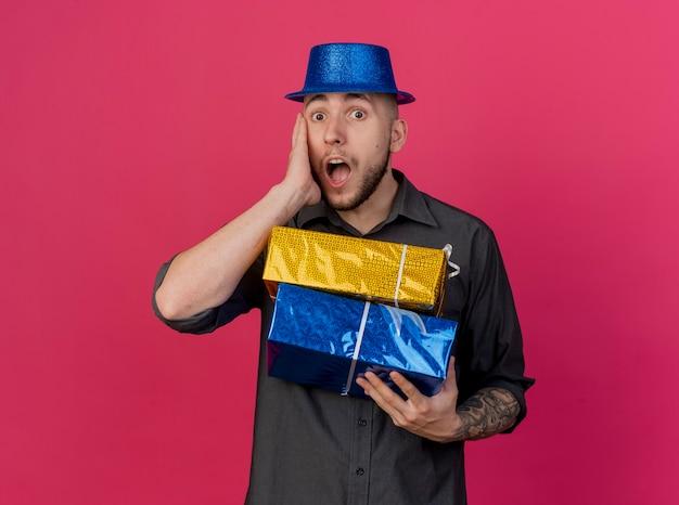 Choqué jeune beau mec de parti slave portant chapeau de fête tenant des paquets-cadeaux regardant la caméra toucher le visage isolé sur fond cramoisi avec espace copie
