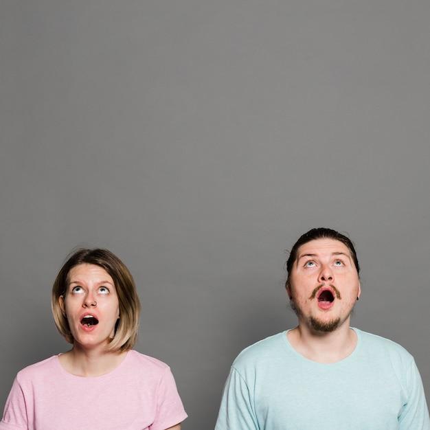 Choqué jeune couple avec la bouche ouverte levant les yeux contre un mur gris