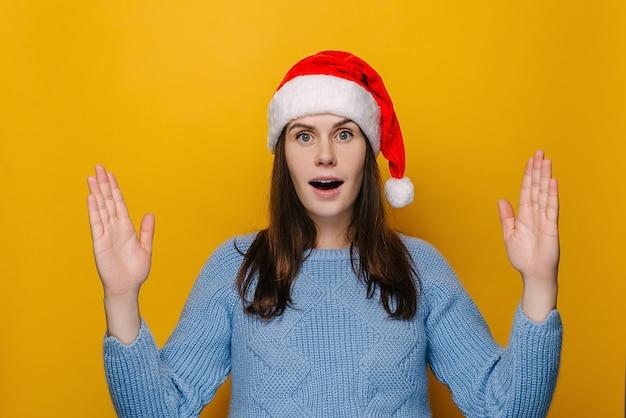 Choqué jeune femme au chapeau de noël montrant un geste de grande taille avec les mains, fille étonnée, porte un pull, isolé sur fond de studio jaune, femme impressionnée démontrer quelque chose