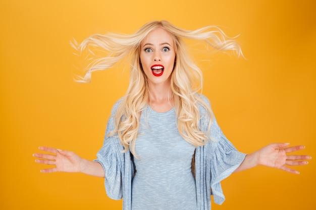 Choqué jeune femme blonde secouant les cheveux.