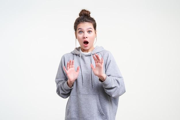 Choqué jeune femme brune attrayante avec maquillage naturel levant les mains en geste de protection tout en regardant la caméra avec étourdissement avec grande bouche ouverte, isolé sur fond blanc