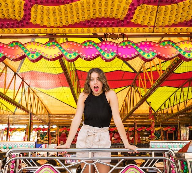 Choqué jeune femme debout au parc d'attractions