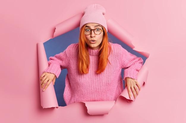 Choqué, une jeune femme européenne rousse gênée halète de merveille voit quelque chose d'incroyable garde les mains sur les côtés du trou déchiré, porte un chapeau rose et un pull en tricot. concept de réactions humaines