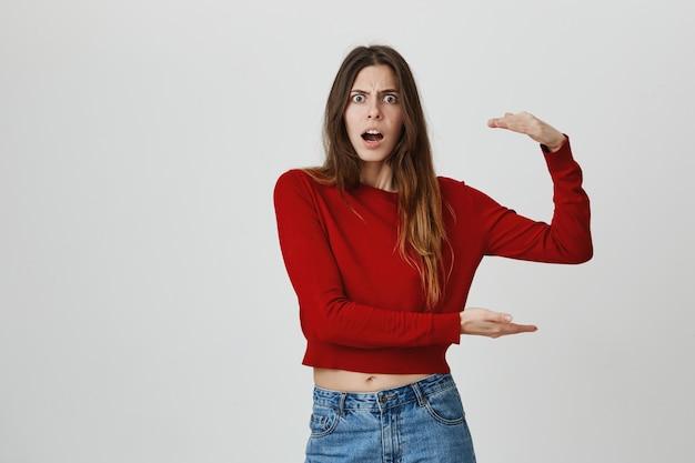 Choqué jeune femme façonnant un gros objet, étonné de la taille