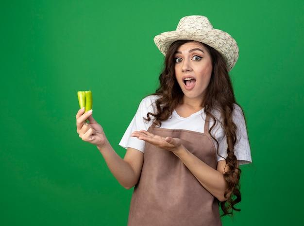 Choqué jeune femme jardinière en uniforme portant chapeau de jardinage détient piment cassé isolé sur mur vert avec espace copie