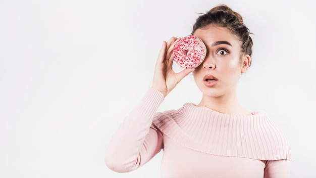 Choqué jeune femme moue ses lèvres qui couvrent les yeux avec beignet sur fond blanc
