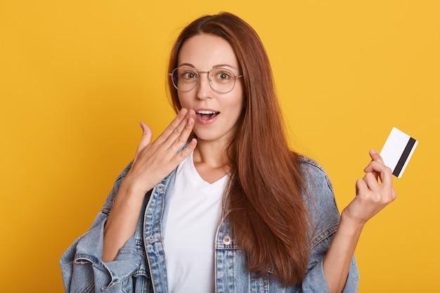 Choqué jeune femme de race blanche avec de longs cheveux raides portant une veste en jean et un t-shirt blanc posant isolé sur mur jaune