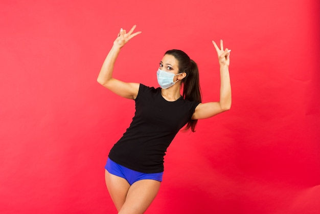 Choqué jeune femme de remise en forme en masque stérile sportswear travaillant isolé sur fond jaune portrait en studio.