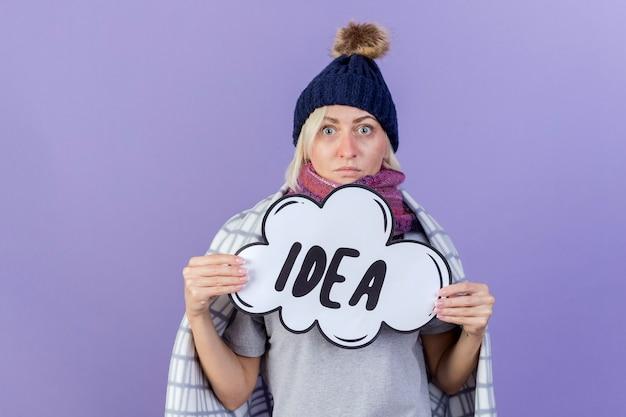 Choqué jeune femme slave malade blonde portant un chapeau d'hiver et une écharpe enveloppée dans un plaid détient bulle idée isolée sur mur violet avec espace de copie
