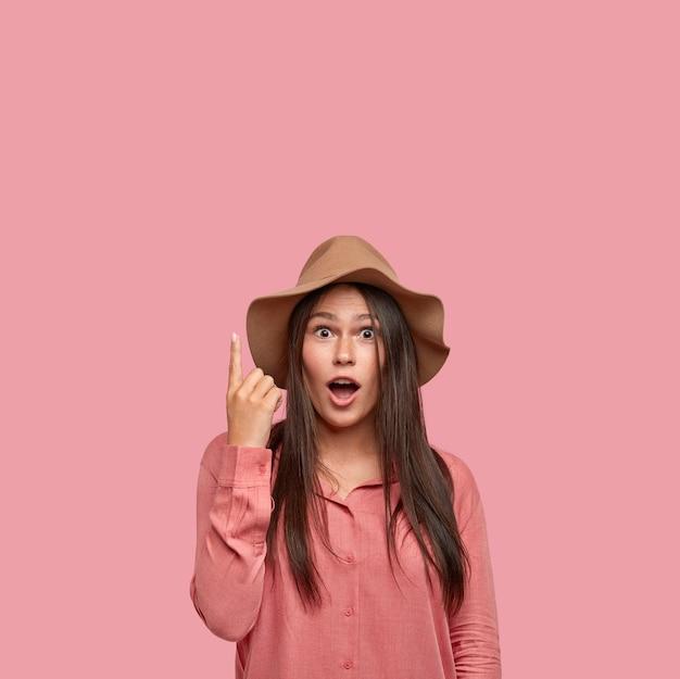 Choqué jeune fille brune vêtue d'un chapeau à la mode, retient son souffle tout en voyant quelque chose d'étonnant et étonné