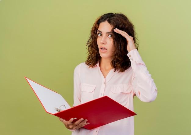 Choqué jeune fille de race blanche met la main sur le front tenant le dossier de fichiers et regardant la caméra isolée sur fond vert avec espace de copie