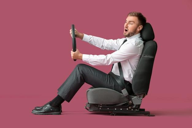 Choqué jeune homme d'affaires avec volant assis sur le siège d'auto sur fond de couleur