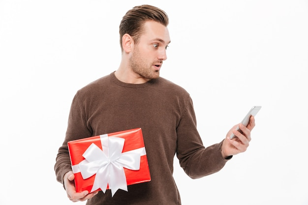 Choqué jeune homme tenant une boîte cadeau surprise